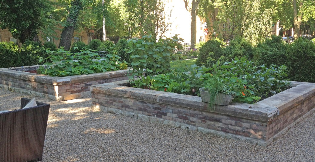 recycled brick planters with stone coping for raised vegetable garden