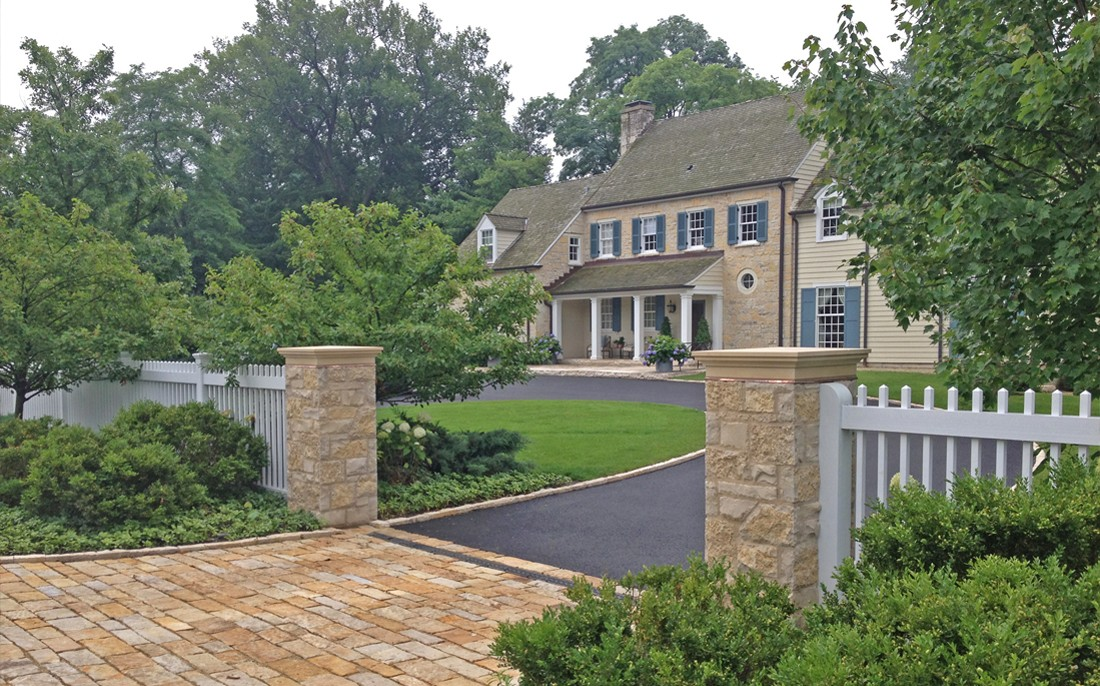 garden entrance with stone columns and white picket fence